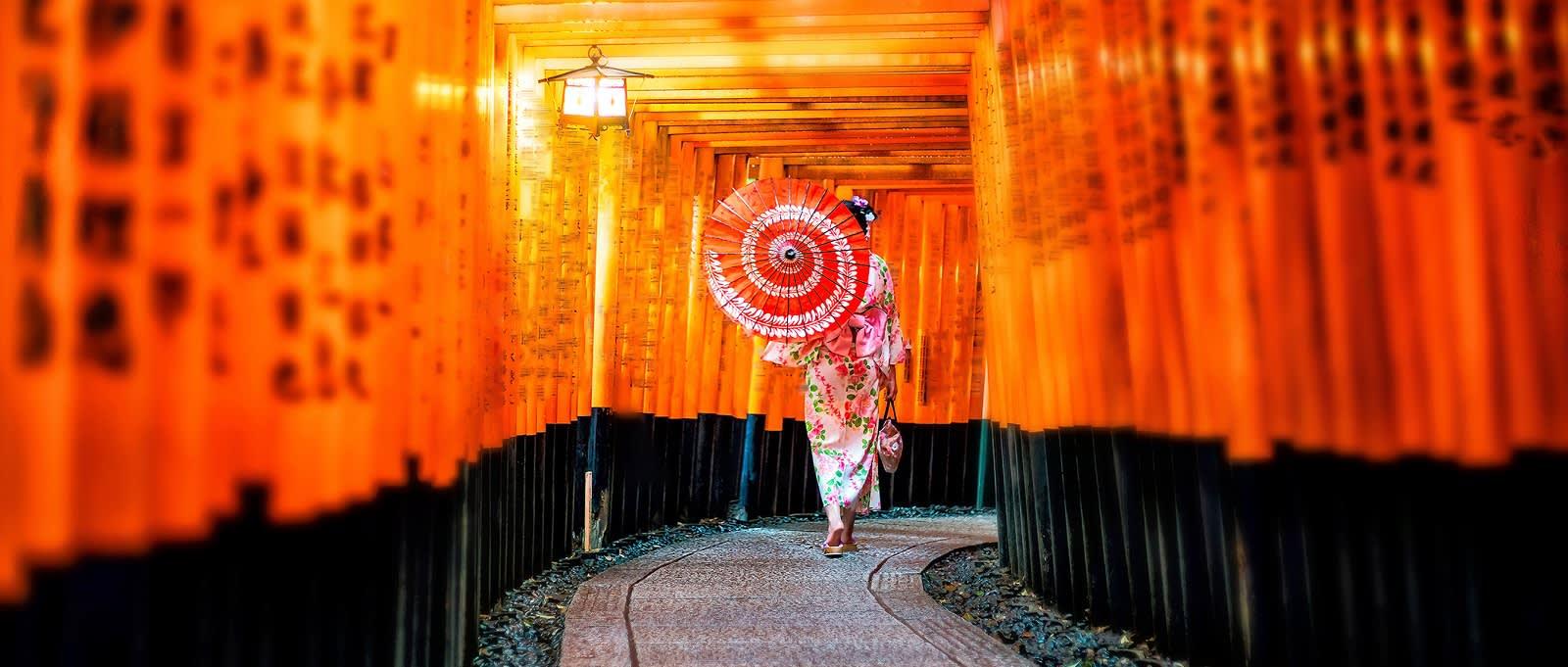 Japanese girl in Yukata with red umbrella at Fushimi Inari shrine in Kyoto, Japan: best time to visit Japan
